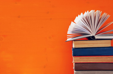 stack of old books in front of wooden background