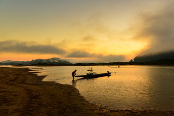 The silluate fisherman casting a net into the water on during sunset,Thailand