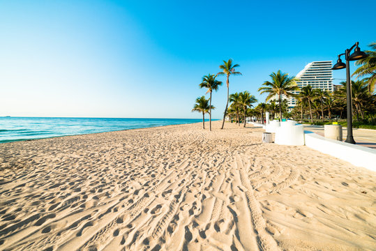 White sand deserted Fort Lauderdale South Florida beach stretching out under beautiful blue cloudless sky