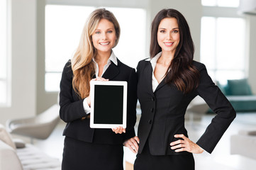 Two businesswomen with digital tablet in office
