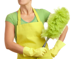 Woman in apron holding green feather duster on white