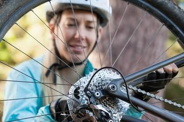 Female mountain biker examining wheel of her bicycle
