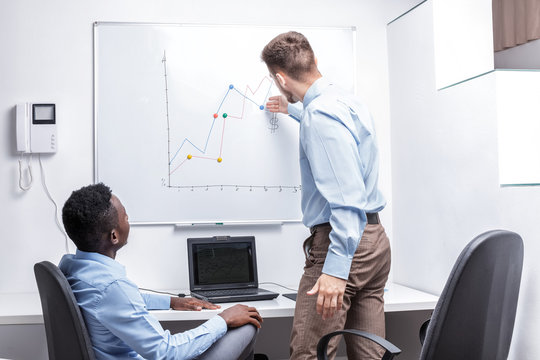 man standing near whiteboard and pointing on the chart