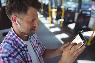 Handsome man listening music on digital tablet