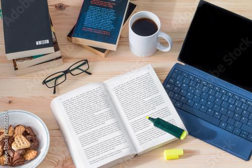 Schreibtisch / Arbeitsplatz mit Buch, Laptop, Kafeetasse und Keksen