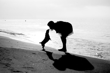 Silhouettes Of Woman And Dog On Beach
