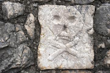 skull and cross bones on the tombstone