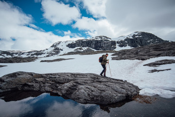 Hiker Hiking On Snow Covered Mountains By Lake Against Cloudy Sky