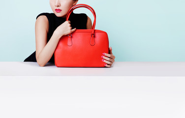 Woman hugging the red bad purse isolated on light blue background. copyspace on the wall and white table.
