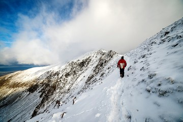 Rear View Of Man Hiking On Snow Trail Against Sky