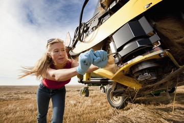 Woman working with equipment for harvesting wheat, Alberta, Canada