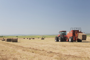 Hay Baler In A Field With Blue Sky, Alberta, Canada