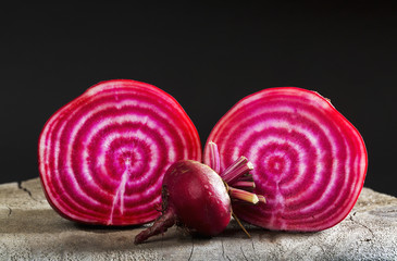 Close up of a cut red and white striped beet with an uncut small beet on top of a wooden board and black background, Calgary, Alberta, Canada
