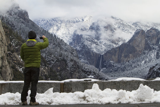 Man wearing a green down jacket, as seen from the back, taking a picture of yosemite valley and bridal veil falls;Yosemite, california, united states of america