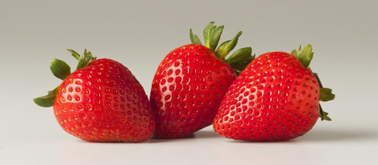 Agriculture - Three strawberries on a white surface.