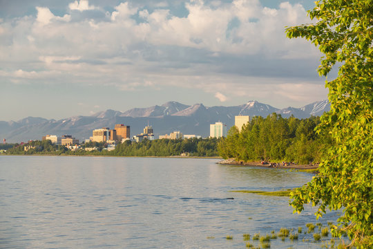 The anchorage city skyline seen from the tony knowles coastal trail during high tide, chugach mountains in the background;Anchorage, alaska, united states of america