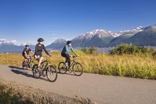 Two women and a man biking on the bird point to girdwood bike trail, turnagain arm;Anchorage, alaska, united states of america