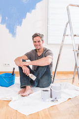 handsome gray haired man painting walls of his new home