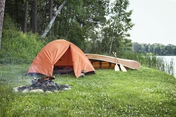 Tent, campfire and canoe on Minnesota lakshore