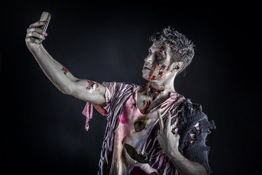 Male zombie using cell phone to take selfie photo, standing on black smoky background, half body shot