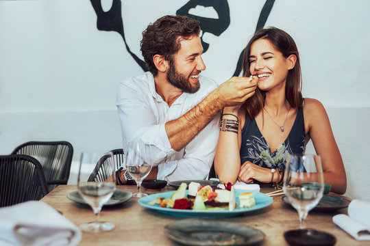 young couple sitting in a cafe and feed each other the juicy cakes