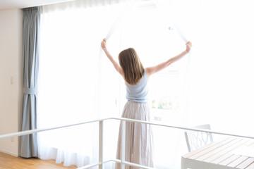 カーテンを開ける女性
