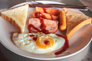 Breakfast with fried eggs, ham and sausages.