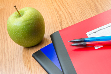 Composition notebooks, with an apple and pencils on a school des