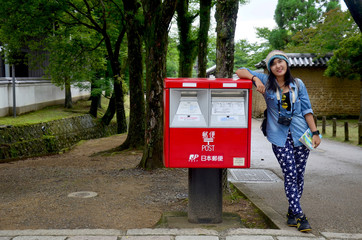 Traveller thai woman portrait with red post box in garden of Tod