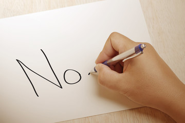 """Male hand writing """"no"""" in capital letters"""