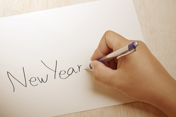 Hand holding a pencil and writing Happy New Year on a white white background
