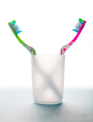 two toothbrushes in a glass