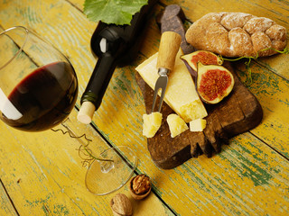 Still life with cheese and red wine on wooden table