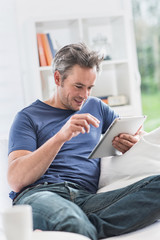 cheerful man at home using a tablet, he sits on a white couch