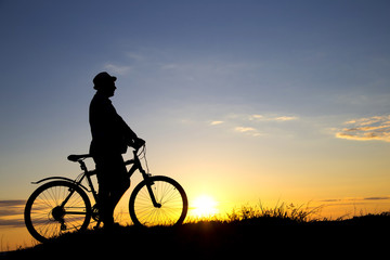 Silhouette of sports person cycling on the field on the beautifu