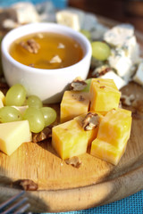 a plate of cheese and honey
