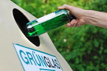 Mensch entsorgt eine Glasflasche in einem Altglas-Container
