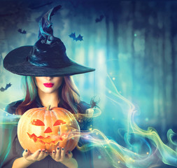 Witch with a Halloween pumpkin in a dark forest