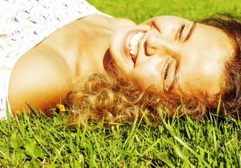 young cute summer girl on green grass outside relaxing happy smiling close up, lifestyle people concept