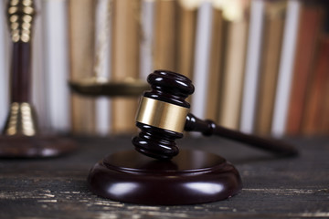 Law book, mallet of the judge, justice scale, wooden desk backgr