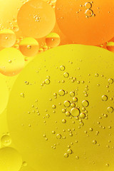 Abstract background of yellow and orange oil droplet on water. Vertically.