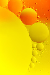 High contrast abstract of oil droplets on water. Small yellow and orange droplets are grouped around a large drop.