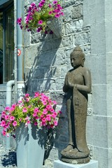 Standing Buddha in front of an entrance.