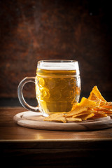 A glass of fresh cold light beer with nachos and wheat in a bar and a dark pub