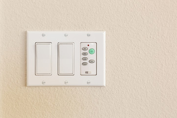 Light Switches and Fan Control on Wall of Home.