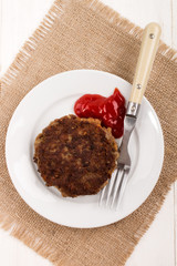 fried rissole on a plate with ketchup