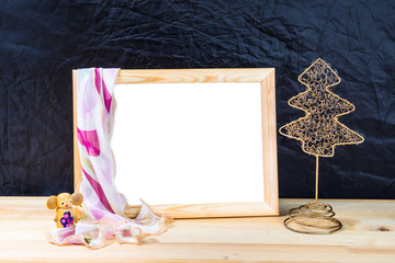 Christmas. Wooden empty picture frame with a white background is on the table. On the frame is scarf. Christmas tree decoration. Wooden toy. Dark blue background.