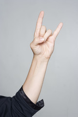 Woman's hand giving the Rock and Roll sign, devil horns gesture
