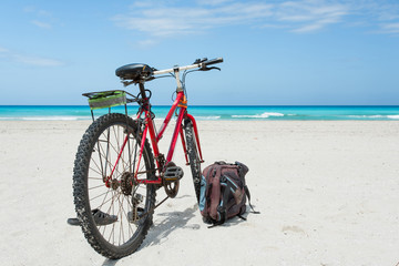 Foto op Plexiglas Fiets Bicycle is perked on the coast of Caribbean Sea with snow-white sand. Backpack and slates lie nearby.