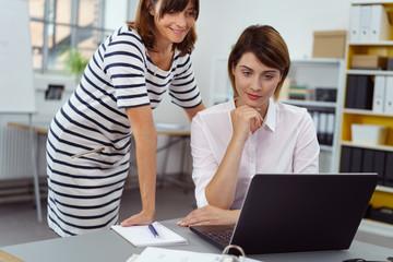 zwei frauen im büro schauen gemeinsam auf laptop